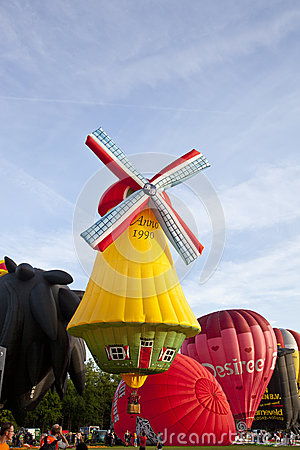 Colorful windmill and red air balloons taking off Editorial Stock Photo
