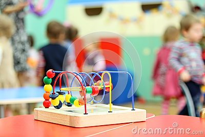Colorful wooden toy stand at table in kindergarten