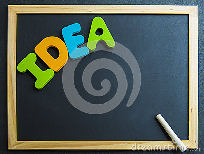 Colorful wooden word Idea on black board with white chalk