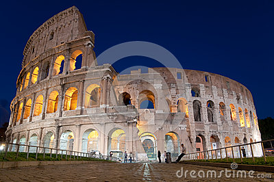 Colosseo and stone street at night in Rome - Italy