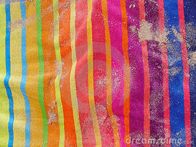 Colourful beach towel with sand