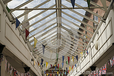 Colourful bunting flags in a glass rooved walkway