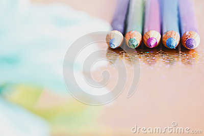 Colourful Eyeliners/pencils With Unfocused Petals Stock Image - Image: 26012081