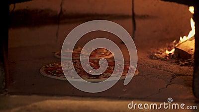 Colpo della pentola del cuoco unico che mette pizza vegaterian nel forno del mattone archivi video