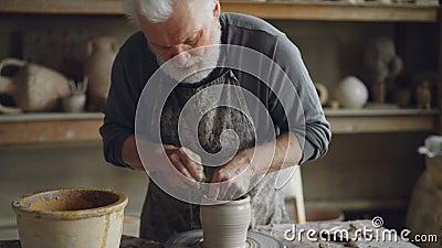 Colpo di inclinazione-su dell'argilla del modanatura del vasaio in artigiano esperto e del vaso professionali di fabbricazione su video d archivio