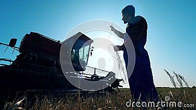 Coltivatore maschile, agricoltore, si trova sul campo accanto al mietitrebbiatore. video d archivio