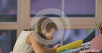 Coluna Cáucaso Cute fazendo lição de casa em casa à noite Loura de vestido bonito sentada à mesa com filme