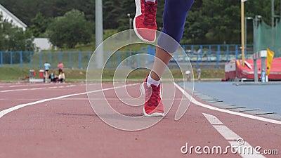 Começos bonitos novos do atleta da mulher que correm na trilha do atletismo durante um treinamento do dia no vídeo do movimento l filme