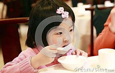 Comer asiático pequeno da menina