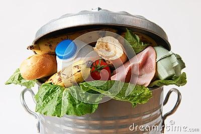 Comida fresca en el cubo de la basura para ilustrar la basura