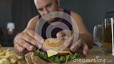 Comiendo excesivamente, hombre obeso que cocina la hamburguesa grande, gastrónomo que admira su comida, primer metrajes