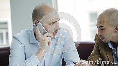 Commerciële vergadering twee collega's op het werk De vergadering van twee zakenlieden en het spreken met een metgezel op de tele stock footage