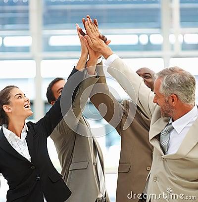 Commercieel team met hun samen opgeheven handen