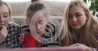 Compagnons de chambre observant le contenu de médias sur l'ordinateur portable tout en ayant le café et le maïs éclaté clips vidéos