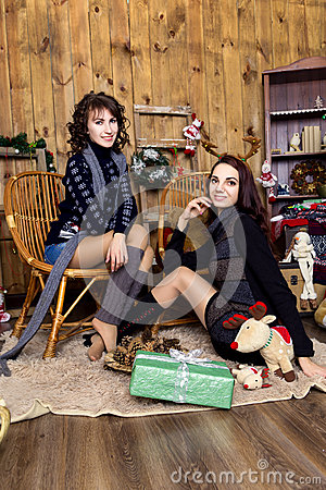 Free Company Of Two Girls With  Gifts In The Room With Wooden Walls. Stock Image - 63797171