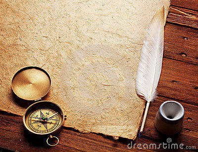 Compass, Inkwell and feather on a old paper