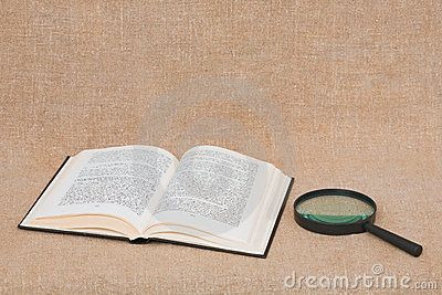 Composition from opened book and magnifier lying