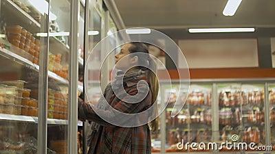 Compra da jovem mulher no supermercado Refrigerador da abertura para escolher o alimento acima refrigerado vídeos de arquivo