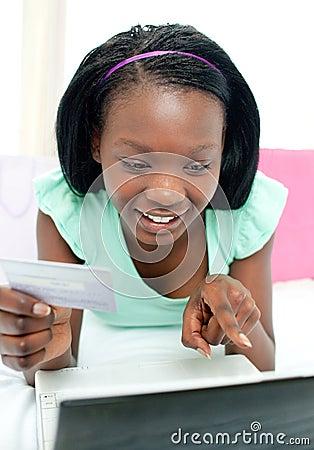 Compras adolescentes alegres de la muchacha en línea
