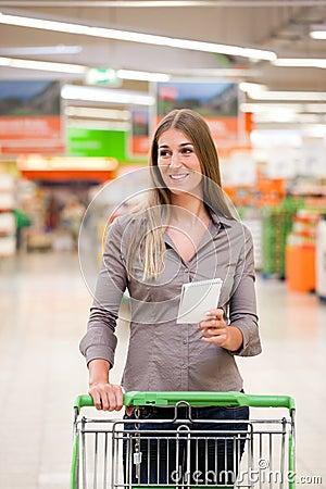 Compras de la mujer con la lista de comprobación y la carretilla