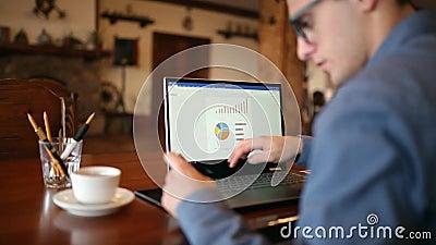Compras del hombre joven en Internet y el pagar con la tarjeta de crédito El hombre de negocios hermoso del freelancer en vidrios metrajes