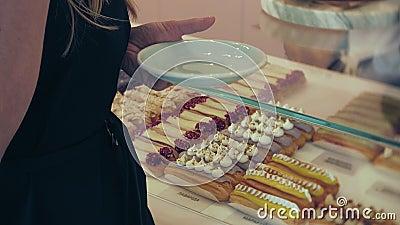 Compratore sceglie squisito Giovane ragazza attraente, buys della donna nella caffetteria o pasticcerie, dolci, dolce, maccherone video d archivio