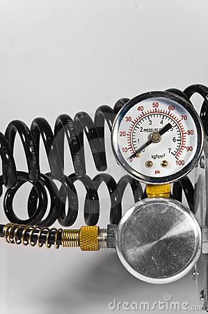 Compressor pressure gauge with black pipes.