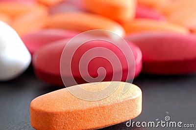 Comprimidos com o comprimido da laranja do close-up