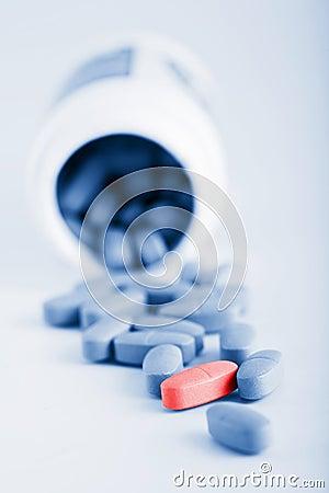 Comprimidos azuis da prescrição com o um comprimido vermelho