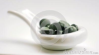 Comprimidos do chlorella de Spirulina que caem na colher branca filme