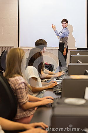 Computer class looking at teacher pointing on projection screen