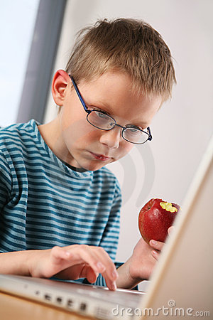 Computer kid. Eating apple