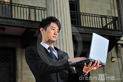 Computer Savvy Asian Executive using a notebook