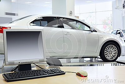 Computer stands on table and new white car