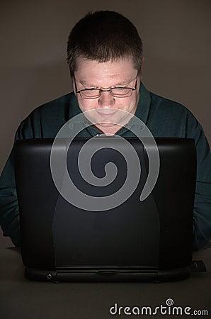 Computer user in darkened room