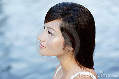 Comtemplative Chinese attractive girl by waters