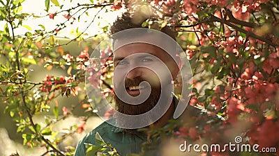 Conceito da harmonia Homem farpado com corte de cabelo à moda com as flores vermelhas no fundo Moderno na camisa verde perto dos  filme