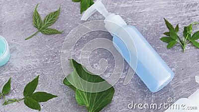 Conceito de produtos de beleza natural, grupo de garrafas de loção rodeadas de folhas verdes com revestimento de câmara vídeos de arquivo