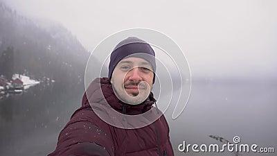 conceito do curso Polegar da exibição do homem acima no lago Ritsa na Abkhásia no inverno filme