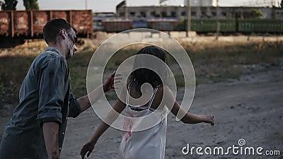 Conceito do película do horror de Dia das Bruxas Imagem do homem assustador e fantasma fêmea ou zombi que andam fora Homem que te filme