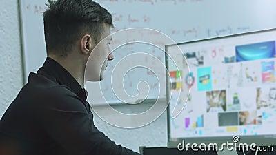 Concentr? sur le travail Vue de côté de jeune homme sûr recherchant l'information sur son carnet tout en se reposant au sien banque de vidéos