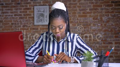Concentrated african woman writting notes and sitting at the workplace near red laptop on brick background.  stock footage