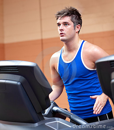 Concentrated athletic man training on a treadmill