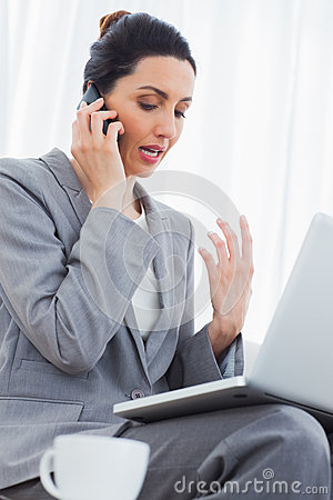 Concentrated businesswoman calling with her mobile phone and using laptop sitting on sofa