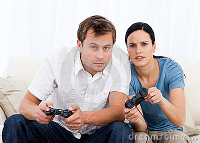 Concentrated couple playing video games together