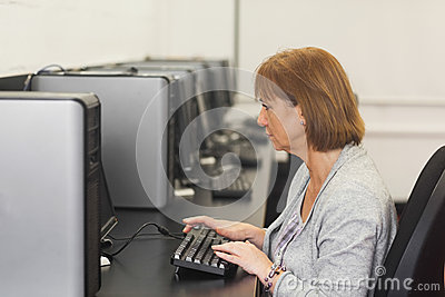 Concentrated female mature student sitting in computer class
