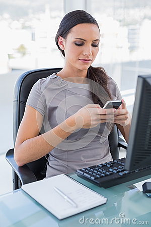 Concentrated gorgeous businesswoman texting on her smartphone