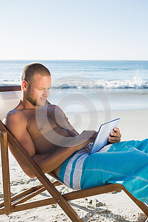 Concentrated handsome man using his tablet while sunbathing