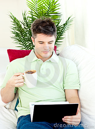 Concentrated man using his laptop drinking coffee