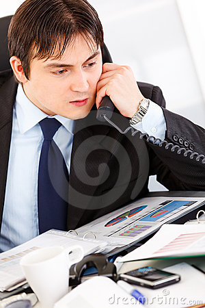 Concentrated modern businessman talking on phone